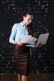 Ung affärskvinna som rymmer en bärbar dator som står på kontor Royaltyfri Fotografi