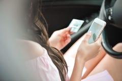 Ung affärskvinna som sitter i bil genom att använda mobiltelefonen arkivfoto