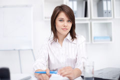 Ung affärskvinna som sitter på skrivbordet på kontoret Fotografering för Bildbyråer