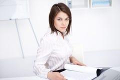 Ung affärskvinna som sitter på skrivbordet på kontoret Royaltyfri Fotografi
