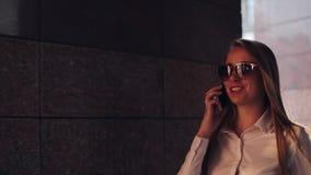 Ung affärskvinna som står near kontorsbyggnad på de soliga stadsgatorna och talar på en mobil mobiltelefon lager videofilmer