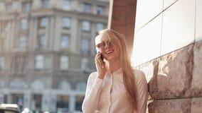 Ung affärskvinna som står near kontorsbyggnad på de soliga stadsgatorna och talar på en mobil mobiltelefon arkivfilmer