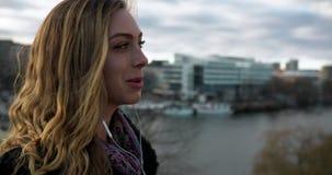 Ung affärskvinna som talar på en hörlurar med mikrofon på en bro i den Stockholm staden lager videofilmer