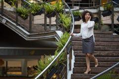 Ung affärskvinna som utomhus talar på den stående mobiltelefonen Arkivbild