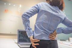 Ung affärskvinna Suffering From Backache i regeringsställning arkivfoto