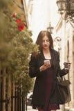 Ung affärskvinnainnehavtelefon och ett kaffe arkivfoto