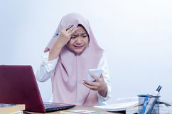 Ung affärskvinnalönelyft ögonbrynen, när kontrollera räkningar royaltyfri fotografi
