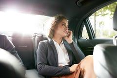 Ung affärskvinnaresande som arbetar i en bil Royaltyfri Fotografi