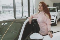 Ung affärskvinnashopping för ny bil på återförsäljarevisningslokalen royaltyfria bilder