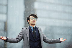 Ung affärsman Enjoying First Snow arkivfoto