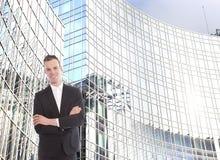 Ung affärsman framme av kontorsbyggnad Fotografering för Bildbyråer
