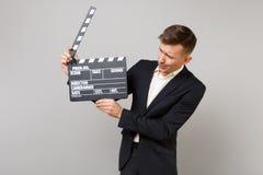 Ung affärsman i den klassiska svarta dräkten som ser på den klassiska svarta filmen som gör clapperboard i isolerade händer på gr fotografering för bildbyråer
