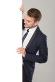 Ung affärsman i den svarta dräkten som ser tom whiteboard royaltyfri fotografi