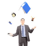 Ung affärsman i en dräkt som jonglerar med kontorstillförsel Arkivbild