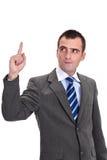 Ung affärsman i en grå dräkt som pekar och ser upp med c Royaltyfria Bilder