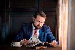 Ung affärsman i en läs- tidskrift för kafé royaltyfri fotografi