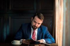 Ung affärsman i en läs- tidskrift för kafé royaltyfri bild