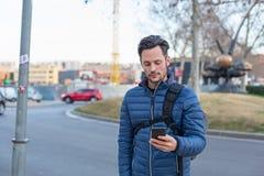 Ung affärsman i gatan med en mobiltelefon och ett blått omslag arkivbilder
