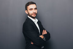 Ung affärsman i korsade händer för dräkt sida royaltyfria foton