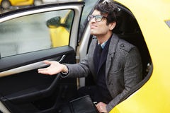 Ung affärsman Leaving Taxi i regn arkivfoto