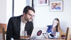Ung affärsman Looking With Interest på skärmen arkivfilmer
