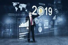 Ung affärsman med bitcoin och numret 2019 fotografering för bildbyråer