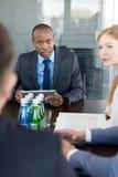 Ung affärsman med den digitala minnestavlan som har diskussion med kollegor på konferenstabellen Arkivbild