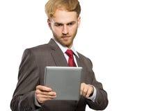 Ung affärsman med en minnestavlaPC, allvarligt uttryck som isoleras Arkivfoton