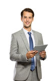 Ung affärsman med en minnestavlaPC, leende, medan stå, isolat Arkivfoton