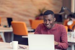 Ung affärsman med ett chockat uttryck som arbetar på en bärbar dator royaltyfria bilder