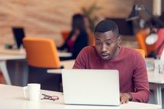Ung affärsman med ett chockat uttryck som arbetar på en bärbar dator royaltyfria foton