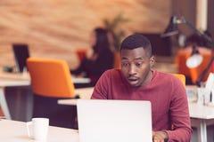 Ung affärsman med ett chockat uttryck som arbetar på en bärbar dator Arkivbild