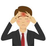 Ung affärsman med huvudvärken som rymmer hans huvud på hans tempel Arkivfoton