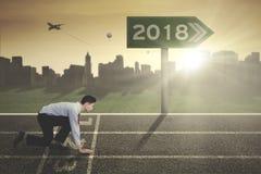 Ung affärsman med nummer 2018 på vägvisaren fotografering för bildbyråer