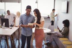 Ung affärsman och affärskvinna som diskuterar över den digitala minnestavlan med kollegor i bakgrund arkivbilder