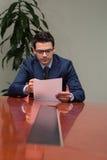 Ung affärsman In Office Looking på papper Royaltyfria Bilder