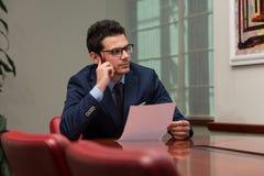 Ung affärsman In Office Looking på papper Royaltyfri Foto