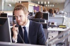 Ung affärsman på arbete i ett upptaget öppet plankontor Arkivfoton