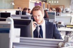Ung affärsman på arbete i ett upptaget öppet plankontor Arkivfoto