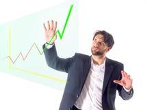 Ung affärsman på en vit bakgrund framme av en faktisk graf Royaltyfria Bilder