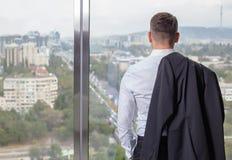 Ung affärsman på kontoret som tillbaka står Arkivfoton