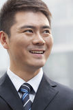 Ung affärsman Smiling och se bort, stående Arkivbild