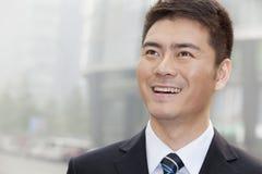 Ung affärsman Smiling och se bort, stående Arkivfoton
