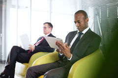 Ung affärsman som använder den digitala minnestavlan på stol med den manliga kollegan i bakgrund på kontoret Fotografering för Bildbyråer