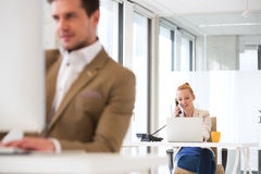 Ung affärsman som använder landlinetelefonen med den manliga kollegan i förgrund på kontoret Arkivbilder