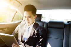 Ung affärsman som använder minnestavlaPC i bil på morgonen royaltyfri foto