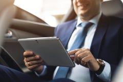 Ung affärsman som använder minnestavlaPC, medan sitta på baksätet av en bil Caucasian manlig affärsledare vid en taxi och royaltyfria bilder