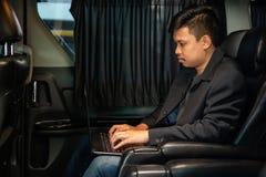 Ung affärsman som använder mobiltelefonen och bärbara datorn i bil royaltyfria foton