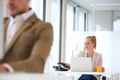 Ung affärsman som använder telefonen med den manliga kollegan i förgrund på kontoret Royaltyfri Bild