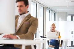 Ung affärsman som använder telefonen med den manliga kollegan i förgrund på kontoret Royaltyfria Bilder